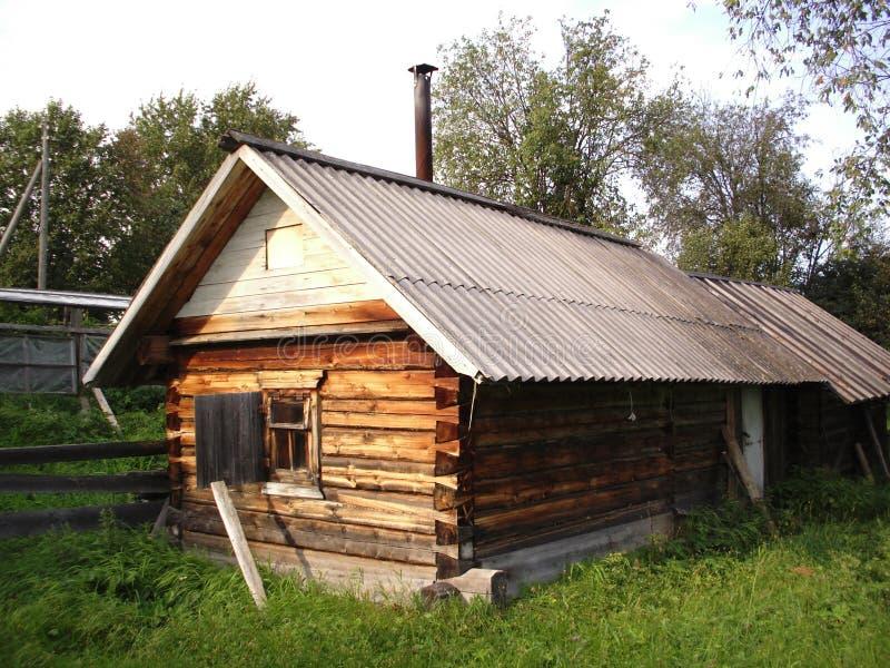 En träryssbathhouse i en by som omges av gräs på a arkivfoto