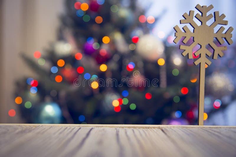 En träsnöflinga på en trätabell mot den dekorerade julgranen royaltyfria foton
