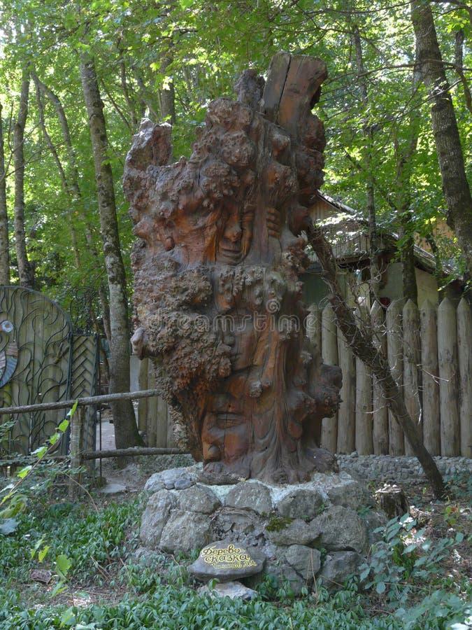 En trästaty kallas ett sagaträd som presenterar olika framsidor på en utställning i parkera royaltyfri foto