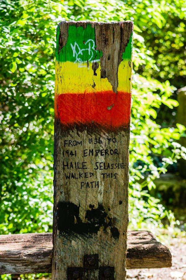 En trästolpe bredvid en bänk i hedersgåva till Haile Selassie i staden av badet arkivfoton