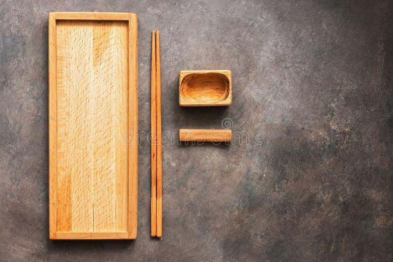 En träuppsättning av disk och kokkonstsushi och rullar för bestick den asiatiska, en rektangulär platta, pinnar och en bunke för  arkivbild