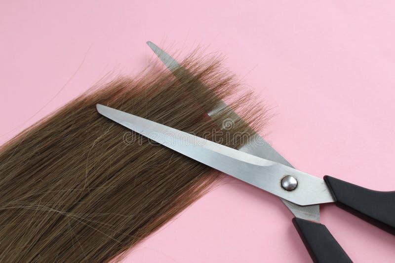 En tråd av hårlögner med sax som klipper sluten arkivbilder