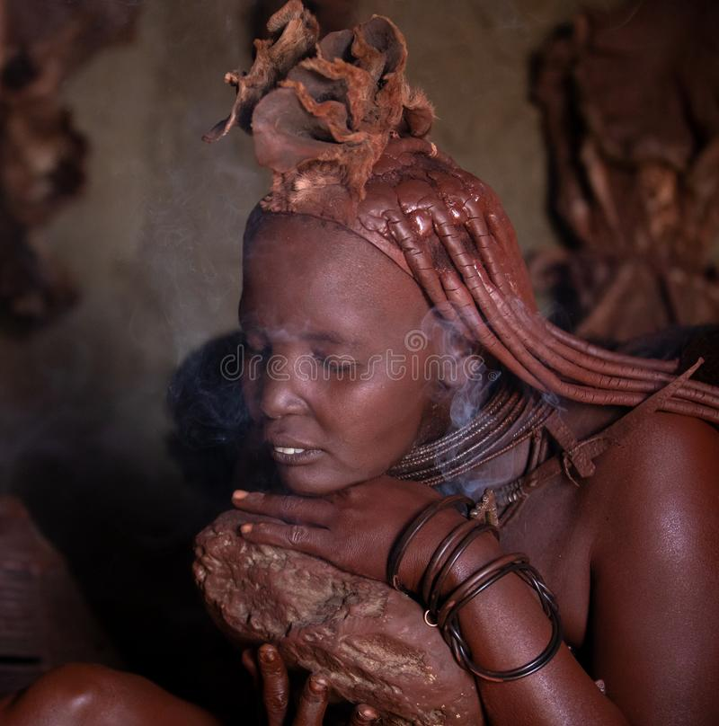 En traditionell himbastamkvinna som gör hennes skönhettillvägagångssätt royaltyfria bilder