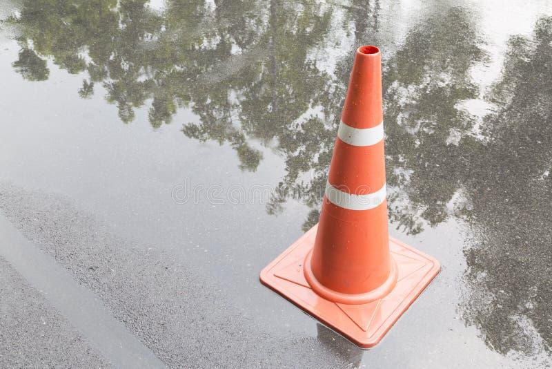 En trafikkotte på vägen i regntid och reflexion royaltyfri fotografi