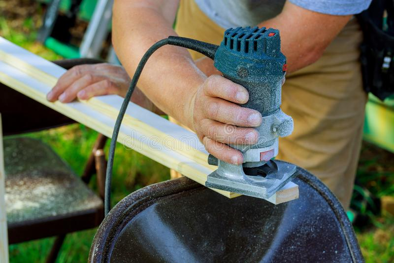 En traitant le charpentier avec le routeur électronique de plongeon des conseils en bois remettez le plan rapproché de coupeur photos libres de droits