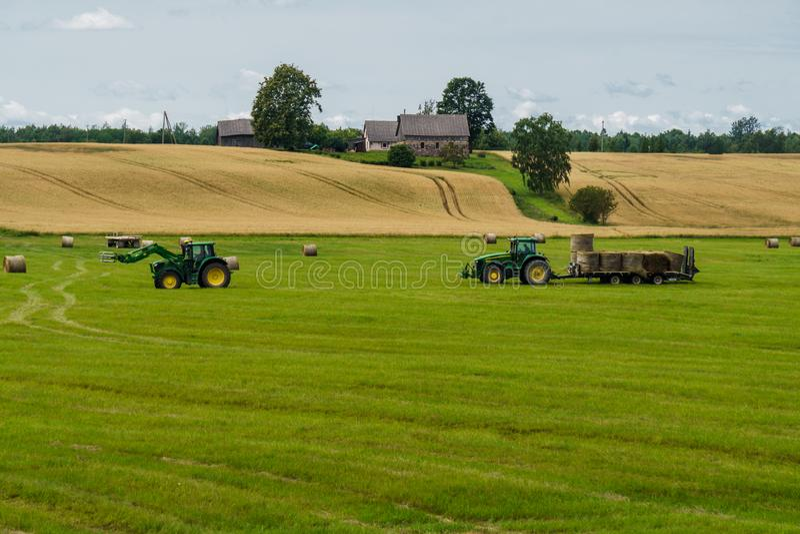 En traktor laddar baler av hö på en släp från en annan traktor fotografering för bildbyråer