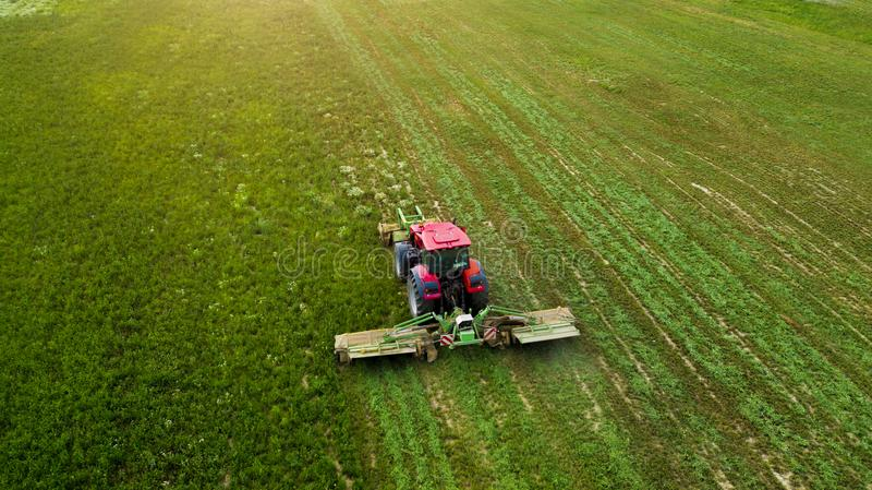 En traktor mejar ett fält av flygfotografering med surret arkivbild