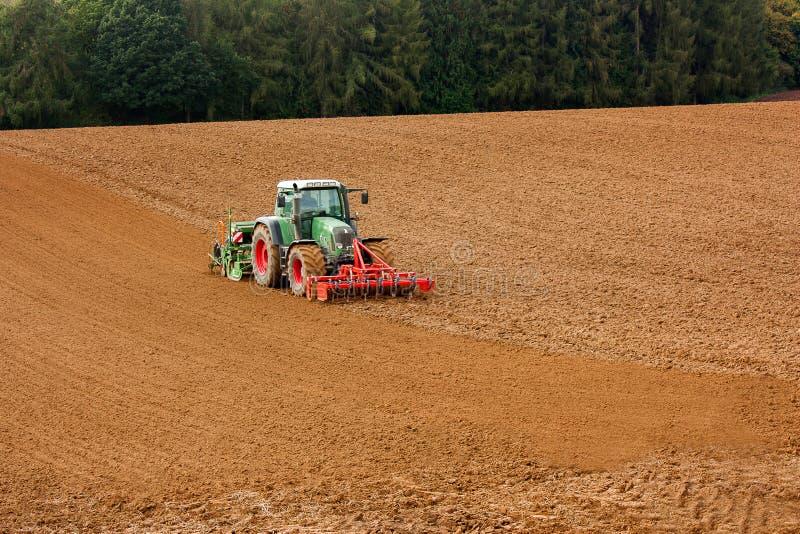 En traktor som plogar jord arkivfoto