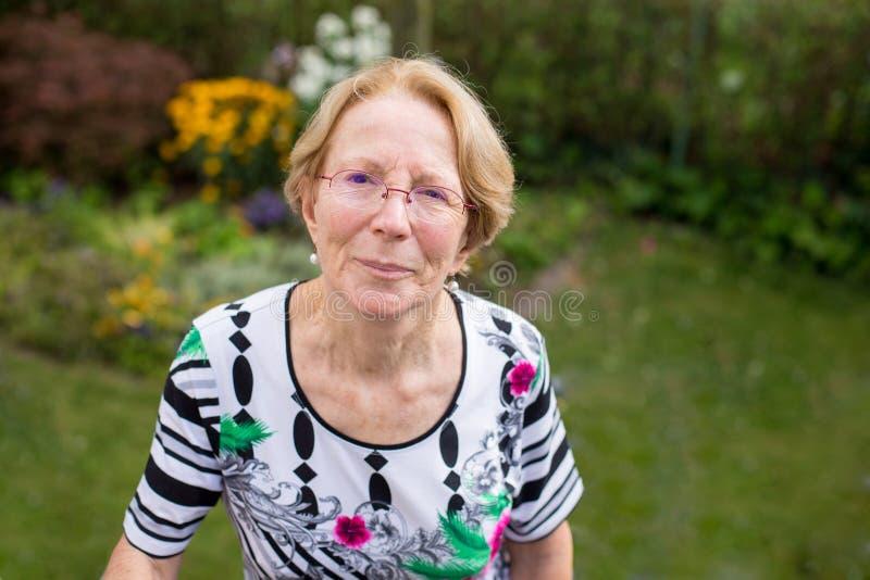 En trevlig äldre kvinna drömmer i härliga gummin fotografering för bildbyråer