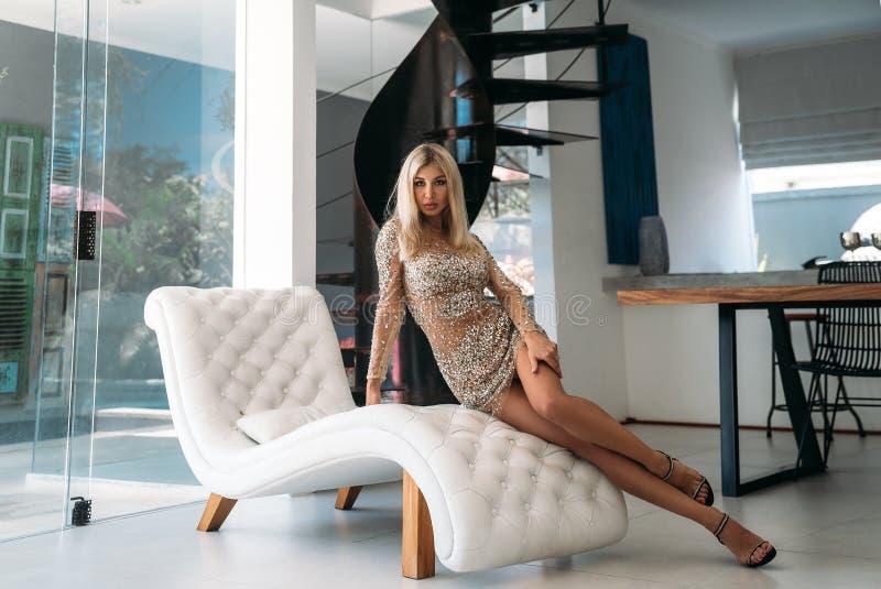 En trevlig flicka med ett härligt diagram i en kort skinande klänning vilar på en vit stilfull soffa i studion Stående av royaltyfri fotografi