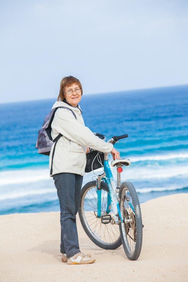 En trevlig hög lady som rider en cykel på stranden. fotografering för bildbyråer