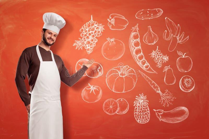En trevlig ung kock i en kockhatt och förkläde som gör en framlägga gest på en bild av frukt och grönsaker på en vägg arkivbild