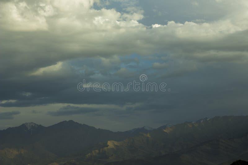 En tung himmel för afton över en bergdal med snö når en höjdpunkt arkivfoton