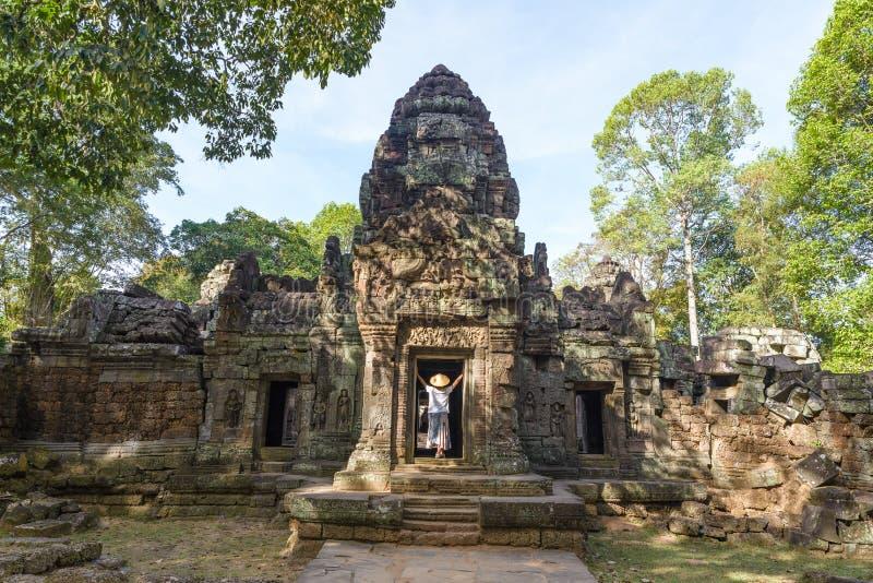 En turist- besöka Angkor fördärvar under djungeln, det Angkor Wat tempelkomplexet, loppdestinationen Cambodja Kvinna med den trad royaltyfri fotografi