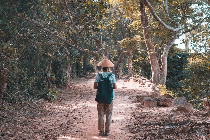 En turist- besöka Angkor fördärvar under djungeln, loppdestinationen Cambodja Kvinna med den traditionella hatten, bakre sikt royaltyfri fotografi