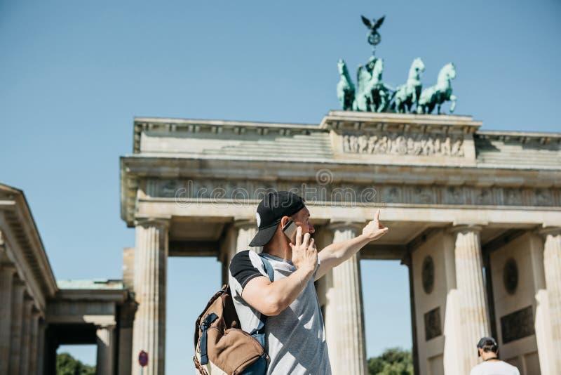 En turist eller en grabb med en ryggsäck talar på en mobiltelefon och visar hans hand på den Brandenburg porten i Berlin royaltyfri bild