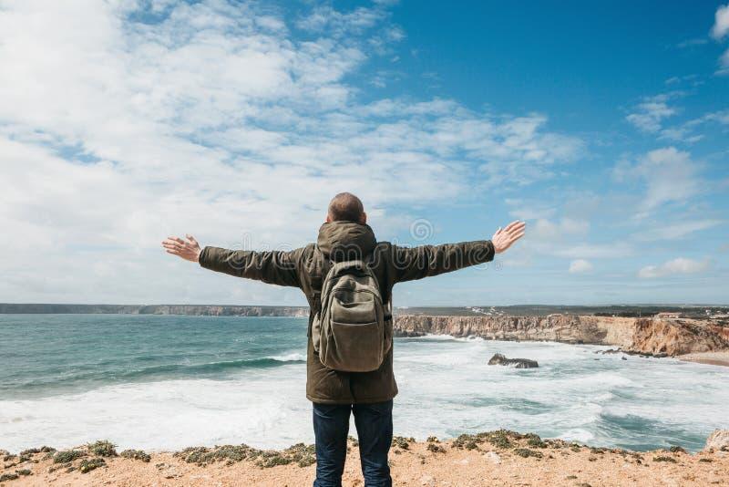 En turist eller en handelsresande med en ryggsäck på den atlantiska kusten i Portugal lyfter upp hans händer royaltyfria bilder