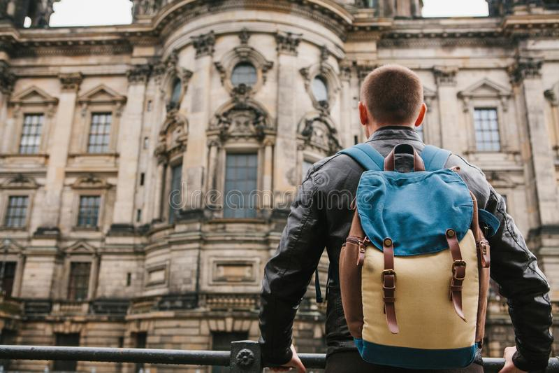 En turist eller en handelsresande med en ryggsäck ser en turist- dragning i Berlin kallade Berliner Dom royaltyfria bilder