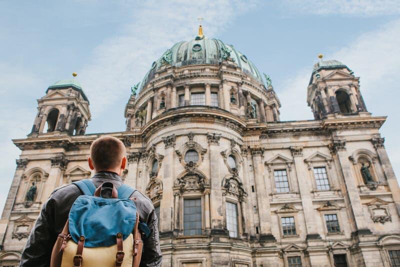 En turist eller en handelsresande med en ryggsäck ser en turist- dragning i Berlin kallade Berliner Dom royaltyfria foton