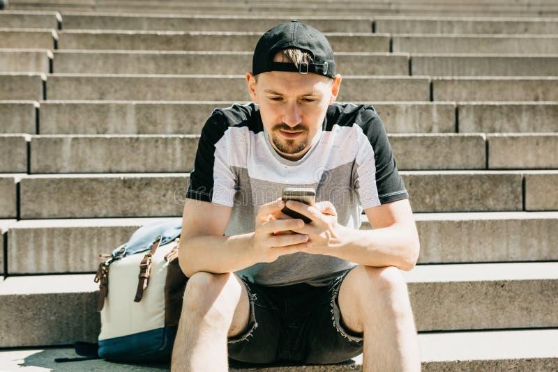 En turist eller en student sitter på trappan, vilar och använder en mobiltelefon arkivfoton