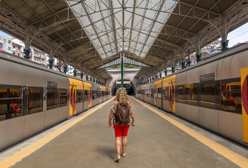 En turist- kvinna med en ryggsäck på henne baksida, promenerar en plattform av stationen för det SaoBento drevet, i staden av Por arkivfoton