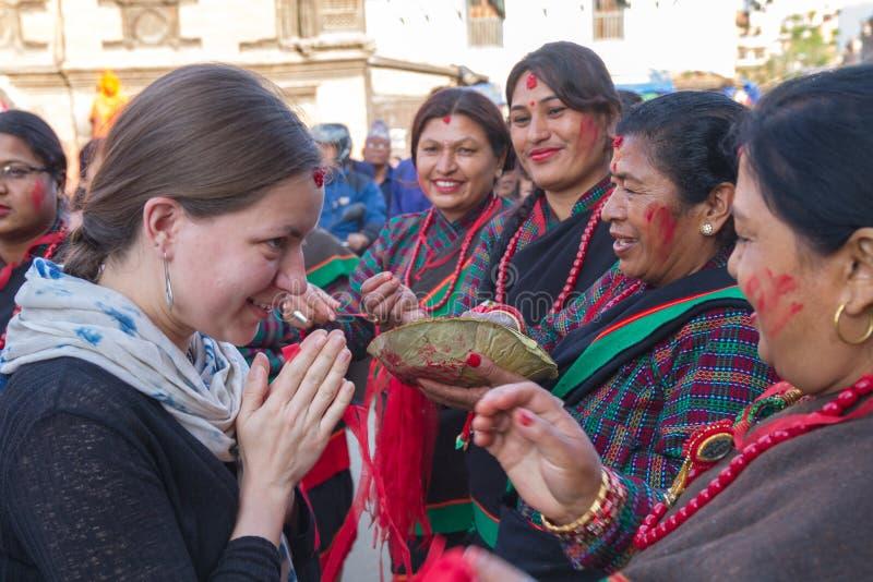 En turist med Nepalikvinnor i Rato Machindranath Jatra royaltyfri fotografi