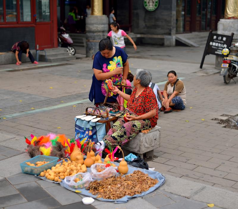 En turist och gamla människor talar om artiklar som säljer konsthantverk royaltyfria foton