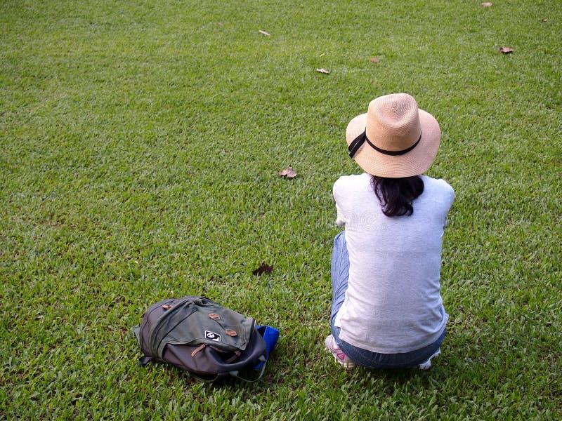 En turist tar en vila på gräset royaltyfri fotografi