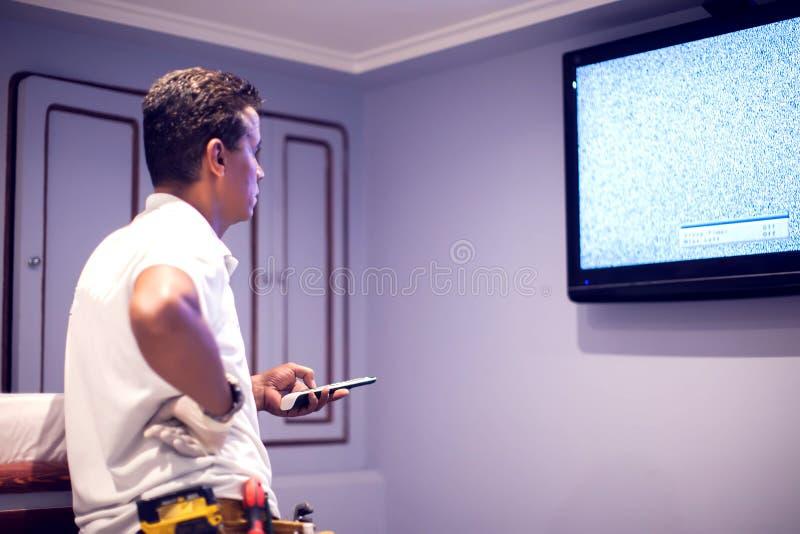 En tv för manarbetarknipa med den blåa skärmen royaltyfri fotografi