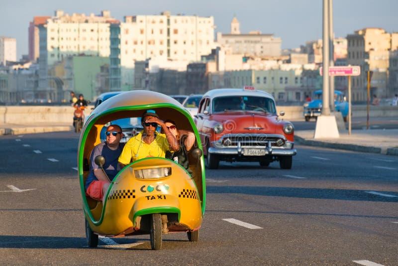 En typisk kubansk mopedtaxi som är bekant som cocotaxi, reser längs den Malecon sjösidaavenyn i havannacigarr royaltyfri foto