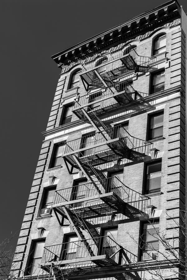 En typisk New York City rödbrun sandsten med brandflykten på förutom byggnaden, i svartvitt, NY, USA arkivbild