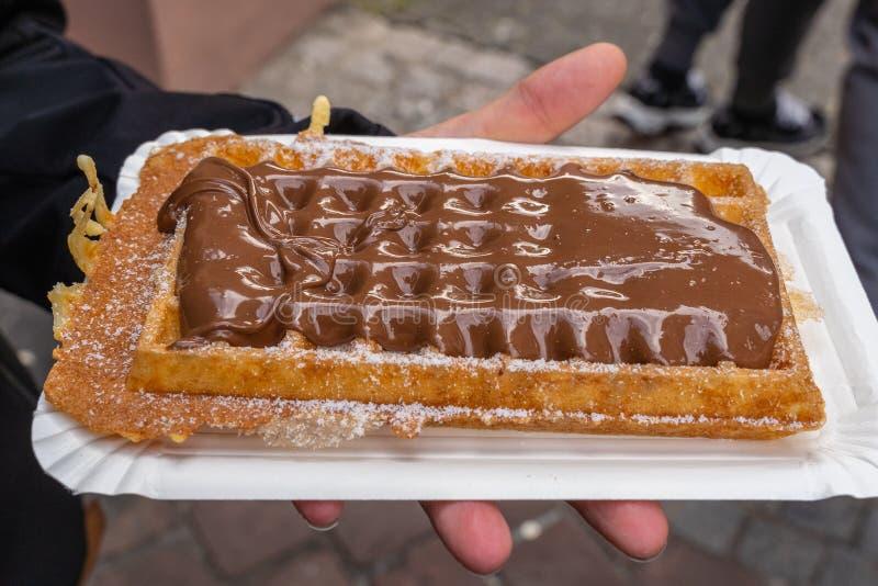 En tysk dillande med bestruken choklad - rymms i en hand royaltyfri fotografi