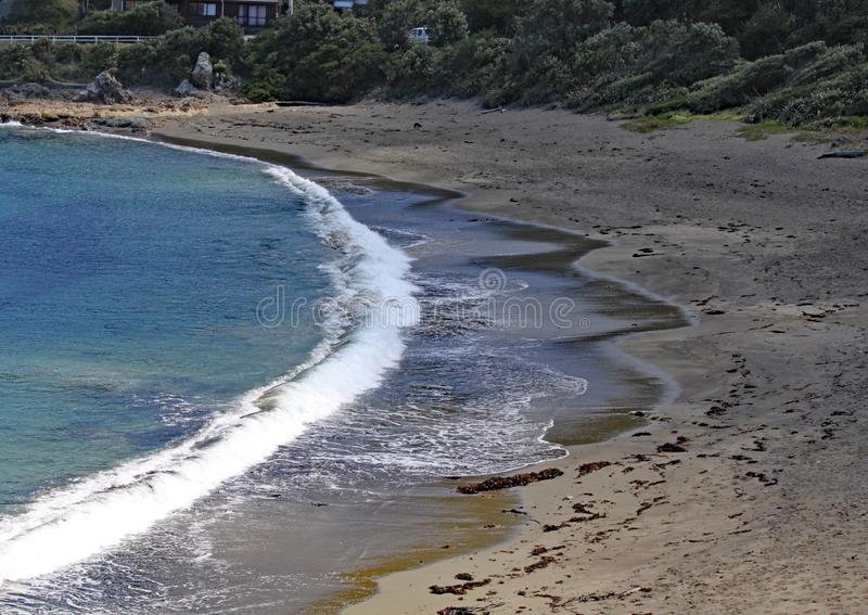 En tyst fjärd med vågor som försiktigt tvättar sig på till stranden nära gummistöveln, Nya Zeeland royaltyfri bild