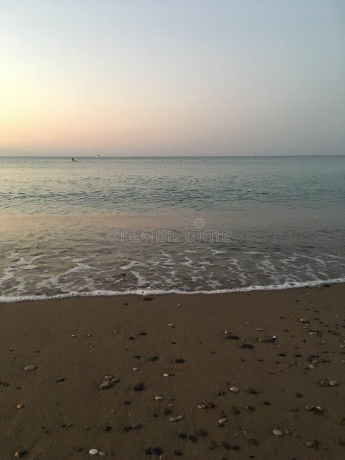 En tyst och öde strand, försiktiga varma vågor som kryper långsamt ut på kusten fotografering för bildbyråer