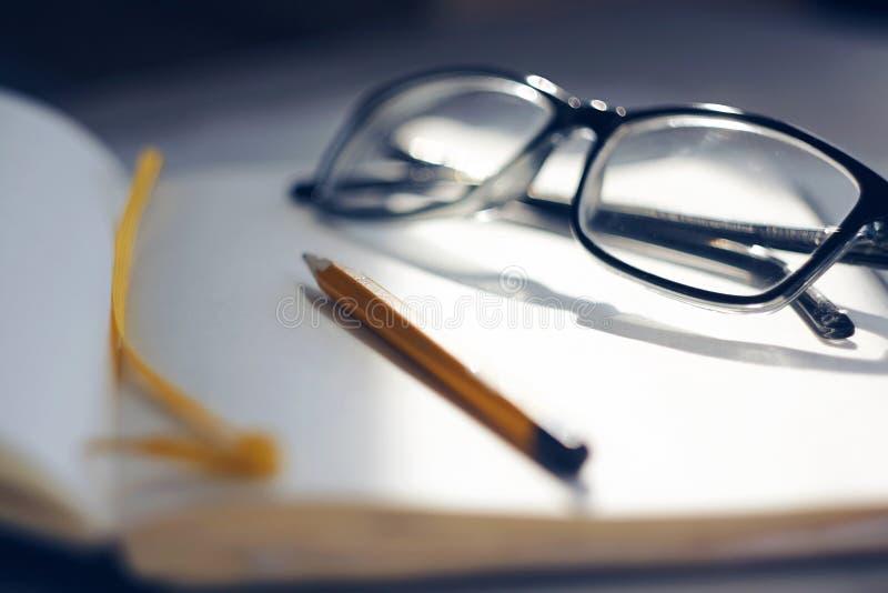 En un cuaderno abierto son los vidrios y un l?piz fotos de archivo