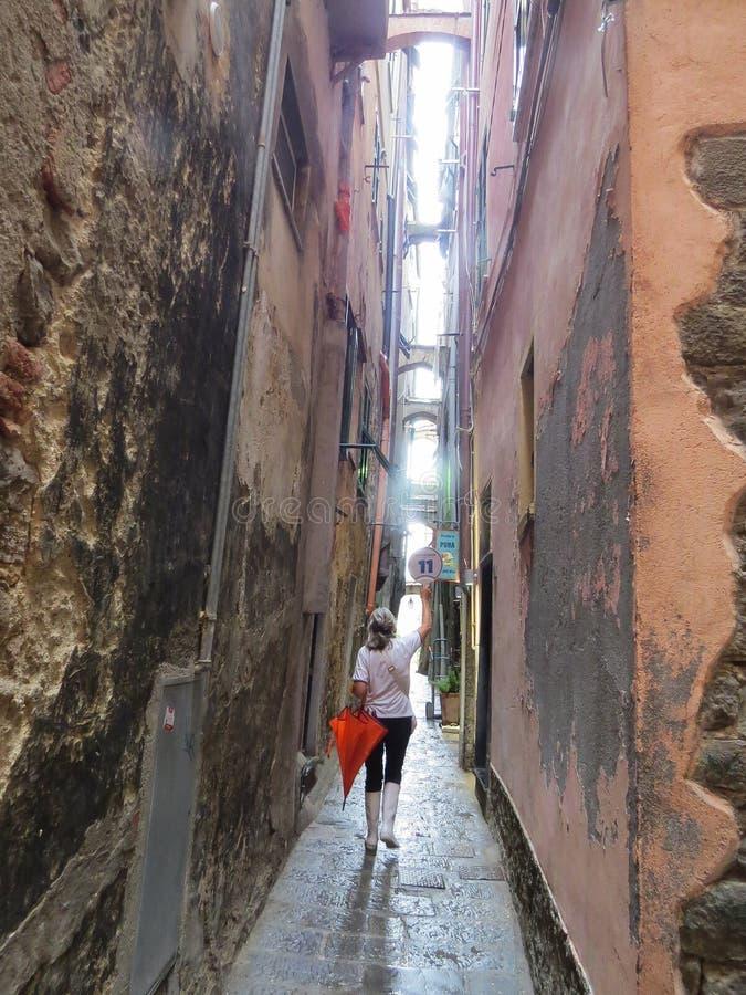 En un día de verano lluvioso, la guía conduce un viaje de la calle estrecha de la ciudad costera de Manarola imágenes de archivo libres de regalías