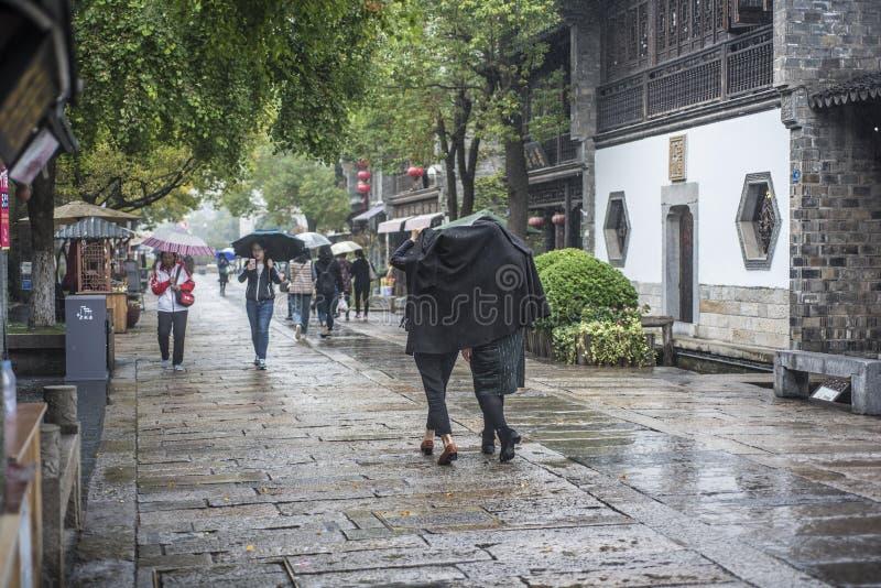 En un día lluvioso, el punto escénico del viejo este de la puerta, dos mujeres jovenes con las chaquetas negras que cubrían sus c fotografía de archivo