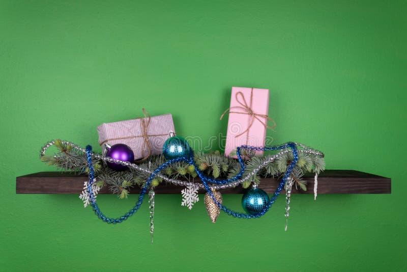En un estante oscuro-coloreado fijado en una pared verde, las ramas coníferas se adornan con los juguetes del Año Nuevo y dos caj imagen de archivo libre de regalías