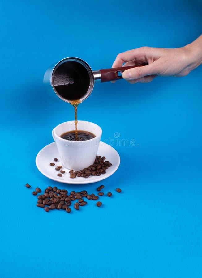 En un fondo azul a la taza con un platillo, granos y un café de colada de la mano imágenes de archivo libres de regalías
