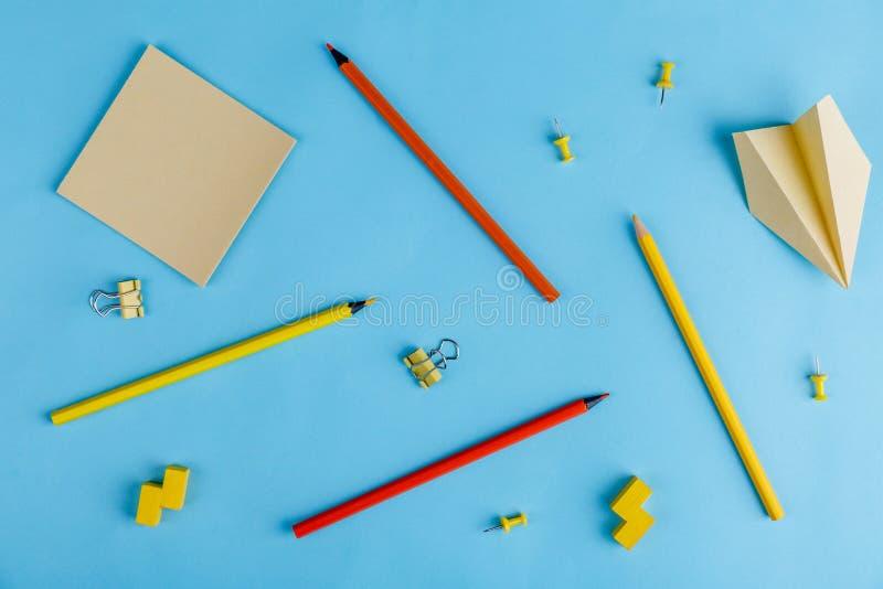En un fondo azul son los lápices multicolores, los clips, las etiquetas engomadas de papel y un aeroplano de papel Visión encima imagen de archivo libre de regalías