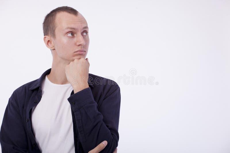 En un fondo blanco un hombre joven ordinario en una camiseta blanca a fotografía de archivo libre de regalías