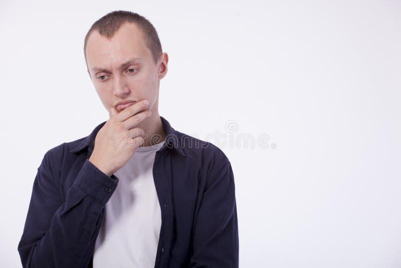 En un fondo blanco un hombre joven ordinario en una camiseta blanca a imagen de archivo libre de regalías
