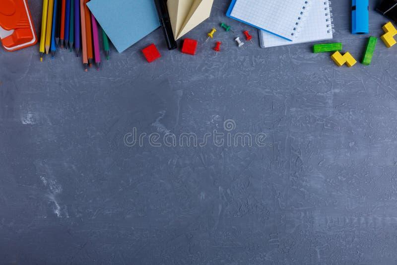 En un fondo con un lugar para la inscripción, la disposición de cuadernos, los lápices coloridos, las pequeñas tizas y los clips fotografía de archivo