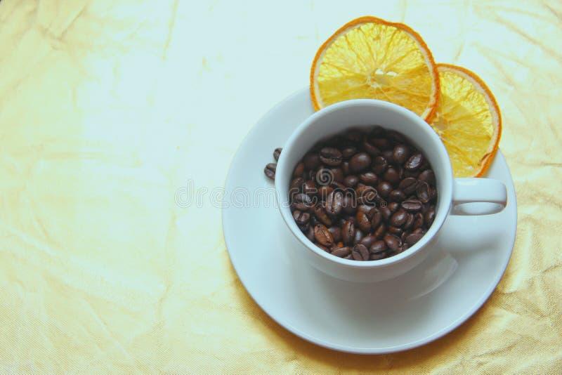 En un fondo del oro, una taza clásica blanca llenada de los granos de café asados con dos rebanadas de naranja secada en un plati imagen de archivo