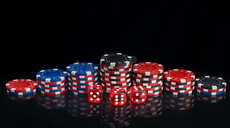 En un fondo negro con la reflexión, pirámides de las fichas de póker multicoloras dispuestas en fila y dados rojos fotografía de archivo libre de regalías