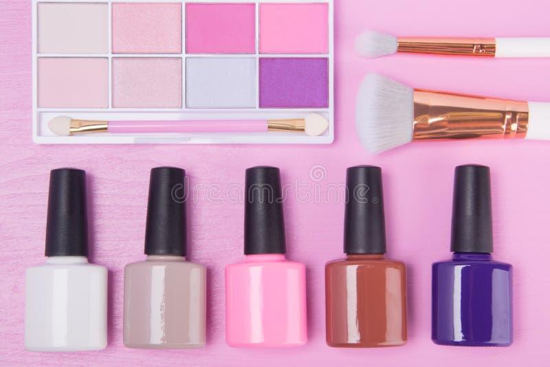 En un fondo rosado, los esmaltes de uñas multicolores están situados en la fila inferior, sombras de ojos y los cepillos están en imagen de archivo
