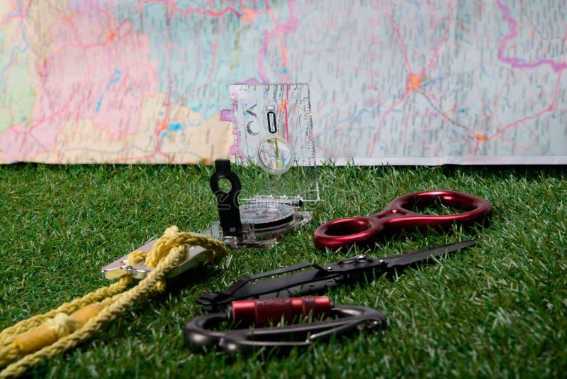 En un fondo verde y mapas, sistema del turista de la mentira, compás, cuchillo, cuerda, mosquetón para subir las montañas fotos de archivo libres de regalías