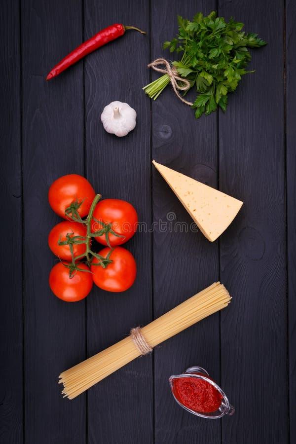 En un sistema de la tabla de los productos para cocinar las pastas con queso y tomates Visión desde arriba dentro fotos de archivo