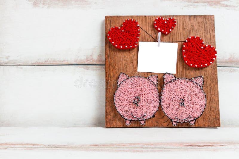 En un fondo blanco, una placa artesanal marrón con la imagen de corazones y cerdos. diseño para tarjeta de felicitación imagen de archivo libre de regalías