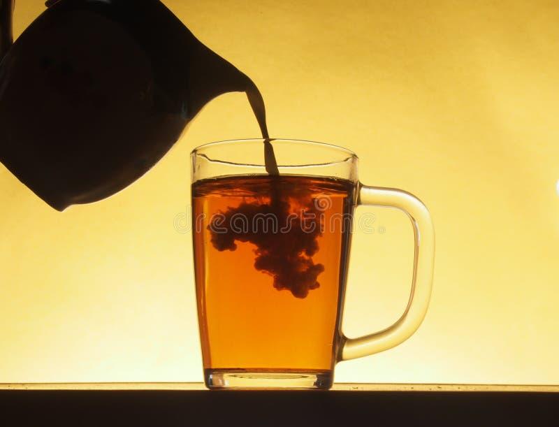 En un vidrio transparente de té vertió la leche de un jarro Partido de té fotos de archivo libres de regalías